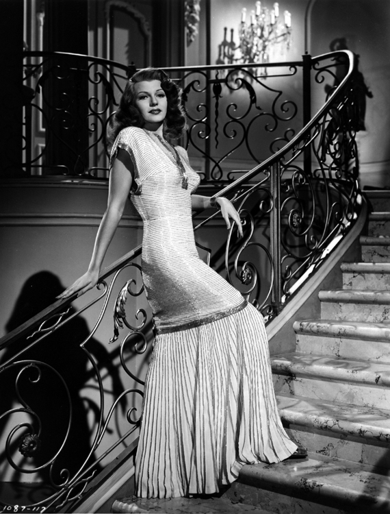 Gilda – Rita Hayworth leans casually against a stair-rail